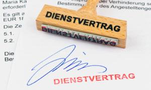 Ein Stempel aus Holz liegt auf einem Dokument. Aufschrift Dienstvertrag